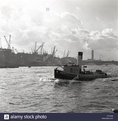 1950s historical, tugboat goes down the river Thames